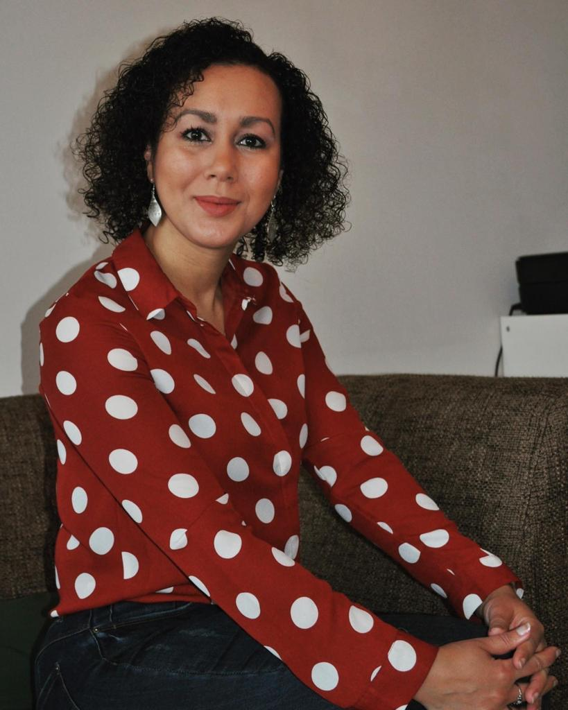 Fatima Akchar op de bank met handen op de knie.